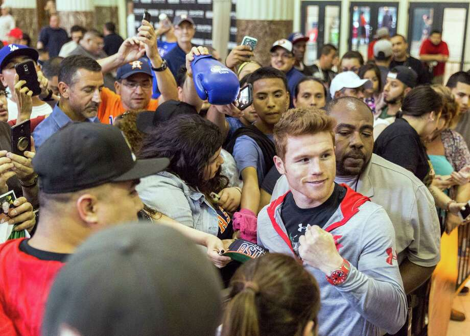 Mexican boxer Canelo Alvarez, right, who will fight James Kirkland at Minute Maid Park on Saturday night, posed for photos and signed autographs for adoring fans at Union Station on Thursday. Photo: Craig Hartley, Freelance / Copyright: Craig H. Hartley