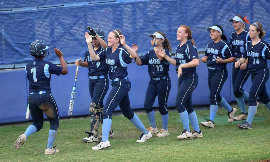 Brianna Stefanic of Johnson is greeted by teammates after scoring a run during game 1 of the Class 6A second-round high school softball series against Southwest at the SAISD complex on Thursday, May 7, 2015. Photo: Billy Calzada, Staff / San Antonio Express-News / San Antonio Express-News