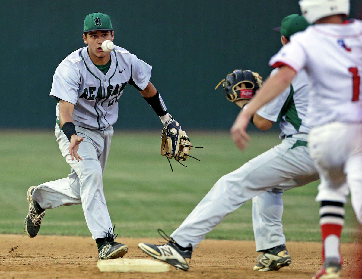 Rattler shortstop Ramon Garza pitches to the second baseman to start a double play as Canyon hosts Reagan in game 1 of a class 6A playoff series at Canyon High School on May 7, 2015.