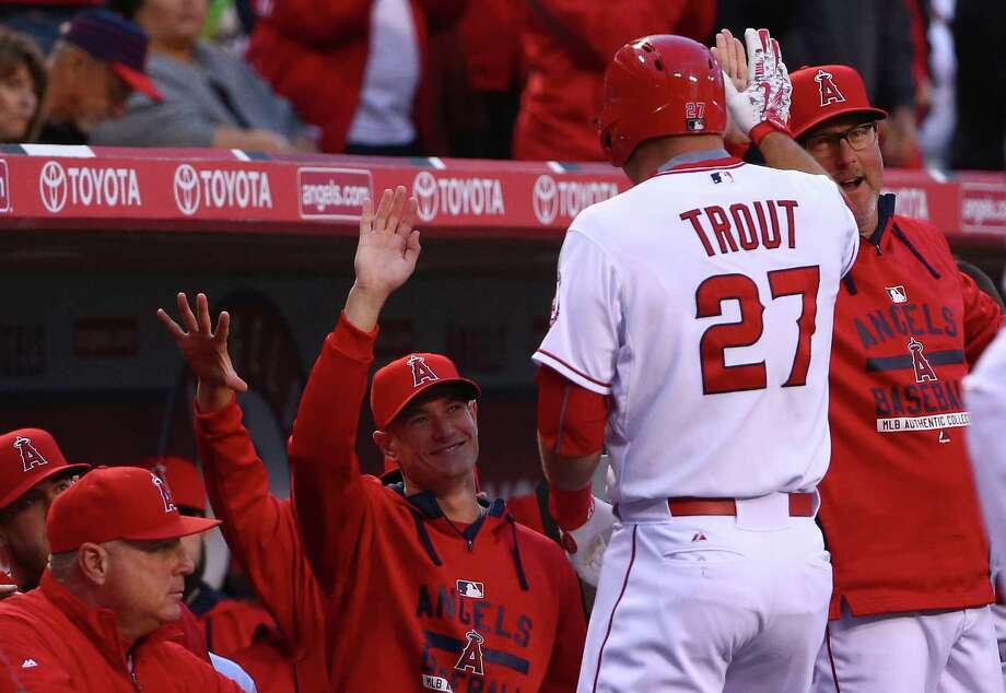 ANAHEIM, CA - MAY 07:  Pitching Coach Mike Butcher high fives Mike Trout #27 of the Los Angeles Angels of Anaheim in the dugout after Trout hit a solo homerun in the first inning against the Houston Astros during the MLB game at Angel Stadium of Anaheim on May 7, 2015 in Anaheim, California.  (Photo by Victor Decolongon/Getty Images) Photo: Victor Decolongon, Stringer / 2015 Getty Images