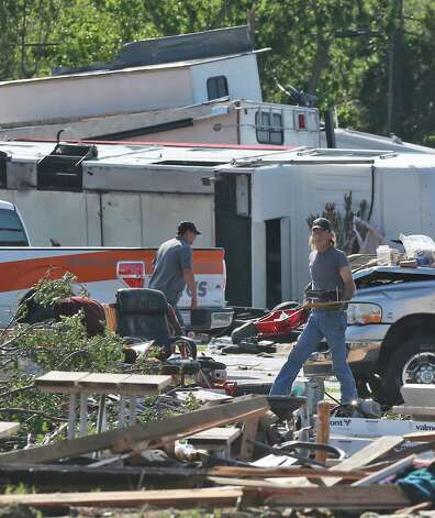 People carry items from recreational vehicles damaged in Wednesday's storm in Oklahoma City, Thursday, May 7, 2015.  Gov. Mary Fallin has declared a state of emergency in 12 Oklahoma counties hit by tornadoes, severe storms, straight-line winds and flooding. (AP Photo/Sue Ogrocki) ORG XMIT: OKSO107 Photo: Sue Ogrocki / AP