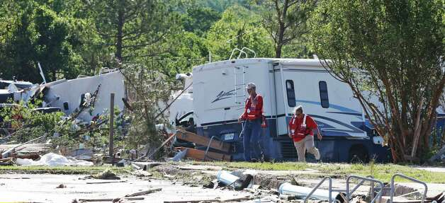 Two Red Cross workers walk past damaged recreational vehicles damaged during Wednesday's storm  in Oklahoma City, Thursday, May 7, 2015.  Gov. Mary Fallin has declared a state of emergency in 12 Oklahoma counties hit by tornadoes, severe storms, straight-line winds and flooding. (AP Photo/Sue Ogrocki)  ORG XMIT: OKSO106 Photo: Sue Ogrocki / AP