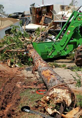 A tree is moved away from damaged recreational vehicles in Oklahoma City, Thursday, May 7, 2015. Gov. Mary Fallin has declared a state of emergency in 12 Oklahoma counties hit by tornadoes, severe storms, straight-line winds and flooding on Wednesday. (AP Photo/Sue Ogrocki) ORG XMIT: OKSO118 Photo: Sue Ogrocki / AP