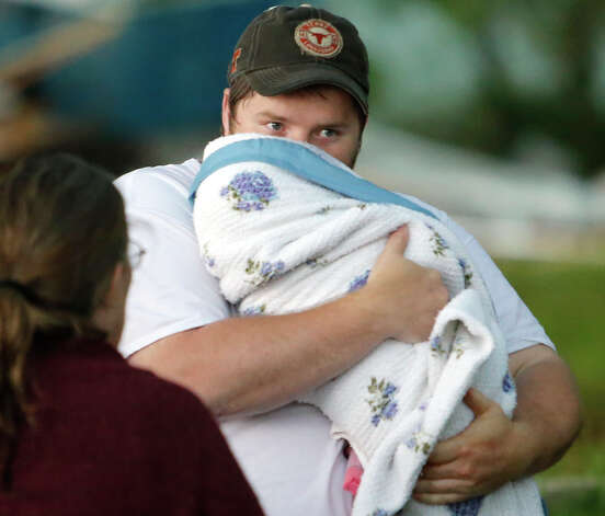 A man holds his son after a tornado ripped through Bridge Creek, Okla. on Wednesday, May 6, 2015. Tornadoes hit Nebraska, Kansas, Oklahoma and north Texas on Wednesday. Most were small and chewed up only farmland, but a pair crossed into Oklahoma City and damaged homes and businesses. A few injuries were reported,  including about a dozen at an Oklahoma City trailer park and one woman drowned in an underground storm shelter that flooded.  (Steve Sisney/The Oklahoman via AP)LOCAL STATIONS OUT (KFOR, KOCO, KWTV, KOKH, KAUT OUT); LOCAL WEBSITES OUT; LOCAL PRINT OUT (EDMOND SUN OUT, OKLAHOMA GAZETTE OUT) TABLOIDS OUT ORG XMIT: OKOKL108 Photo: Steve Sisney / The Oklahoman