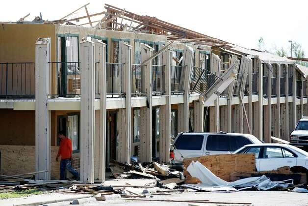 A man walks past a hotel that was damaged in Wednesday's storm in south Oklahoma City, Thursday, May 7, 2015. Tornadoes hit Nebraska, Kansas, Oklahoma and north Texas on Wednesday. Most were small and chewed up only farmland, but a pair crossed into Oklahoma City and damaged homes and businesses. A few injuries were reported,  including about a dozen at an Oklahoma City trailer park and one woman drowned in an underground storm shelter that flooded.  (Steve Gooch/The Oklahoman via AP) LOCAL STATIONS OUT (KFOR, KOCO, KWTV, KOKH, KAUT OUT); LOCAL WEBSITES OUT; LOCAL PRINT OUT (EDMOND SUN OUT, OKLAHOMA GAZETTE OUT) TABLOIDS OUT     ORG XMIT: OKOKL103 Photo: Steve Gooch / The Oklahoman