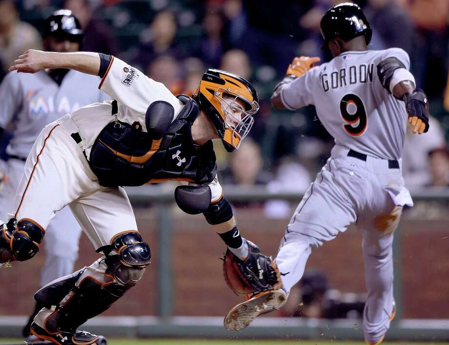 SAN FRANCISCO, CA - MAY 07:  Dee Gordon #9 of the Miami Marlins scores just avoiding the tag of Buster Posey #28 of the San Francisco Giants in the top of the ninth inning at AT&T Park on May 7, 2015 in San Francisco, California. The Marlins won the game 7-2. (Photo by Thearon W. Henderson/Getty Images) Photo: Thearon W. Henderson / Getty Images / 2015 Getty Images