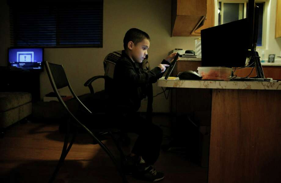 Eric Mendez, 7, uses the iPad given to him by the San Francisco Unified School District after his father went through a district training program. Photo: Carlos Avila Gonzalez / The Chronicle / ONLINE_YES