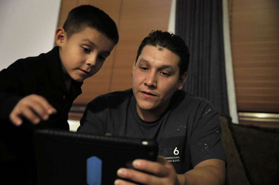 Eric Mendez, right, and his son, Eric, 7, use the iPad given to them by the San Francisco Unified School District to do his studying at a relative's home in San Lorenzo, Calif., on Thursday, May 7, 2015. iPads were given to first graders in four San Francisco schools through a donation made by Facebook founder Mark Zuckerberg. Photo: Carlos Avila Gonzalez / The Chronicle / ONLINE_YES