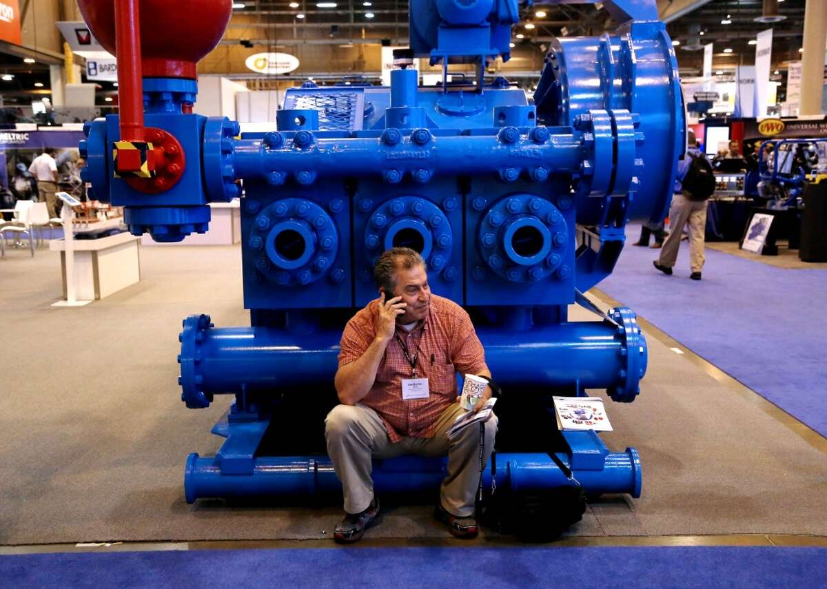 Norberto Marin, an independent consultant, of California, does business while sitting on a piece of machinery in the Offshore Technology Conference at the NRG Center Thursday, May 7, 2015, in Houston, Texas. ( Gary Coronado / Houston Chronicle )