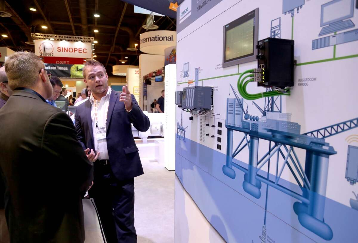 Jeffrey Jensen, an oil and gas engineer, shows conventioneers Siemens SIMATIC HMI, human machine interface, S7-1500 PLC, programmable logic controller, used to monitor well heads to prevent a blowout, in the Siemens booth in the Offshore Technology Conference at the NRG Center Thursday, May 7, 2015, in Houston, Texas. ( Gary Coronado / Houston Chronicle )