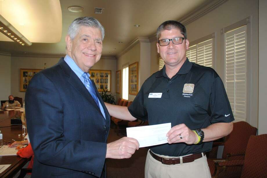 Gilbert Baker, (left) of the AFP Group in Houston, presented a $3,000 check from the Million Dollar Round Table Foundation to HomeAid board president Greg Tomlinson at a recent HomeAid board meeting.