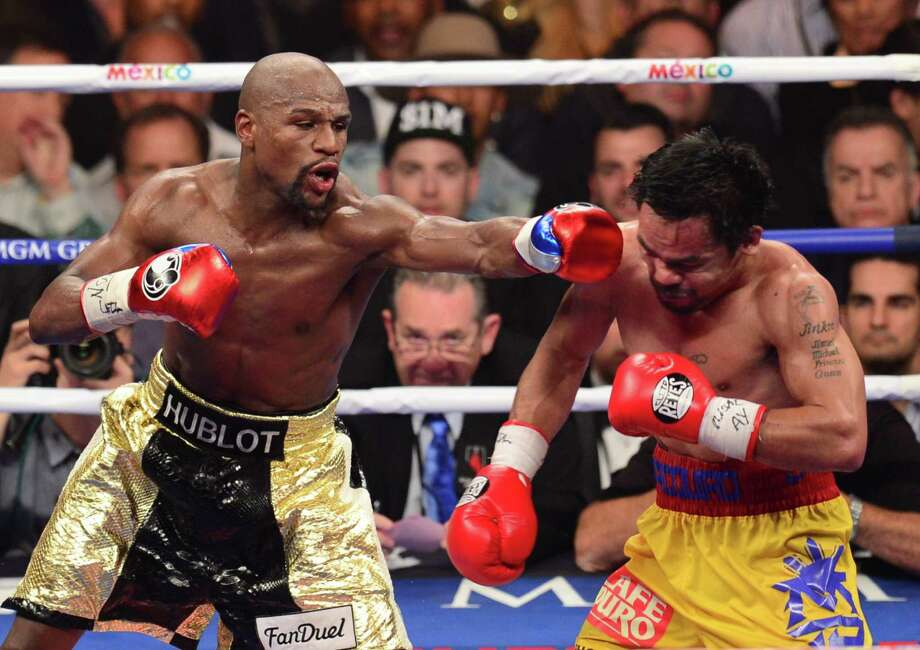 Floyd Mayweather Jr. (L) connects against Manny Pacquiao (R) during their welterweight unification bout on Saturday. Organizers and promoters — which included Top Rank Inc., Mayweather Promotions, Showtime and HBO — arranged to have someone sing the Mexican national anthem before the May 2 bout. At least there was no sombrero. Photo: FREDERIC J. BROWN /AFP / Getty Images / AFP