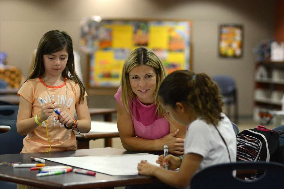 Kelly Swanson, center, parent volunteer and founder of the Reynolds Elem. Humanitarian Club, leads her daughter Maria, 8, left, and Nour Roberts Nisim, 9, right, both third graders, in their poster making session to publicize the club's soldier care package drive during their club meeting on April 28, 2015. Photo: Jerry Baker, Freelance