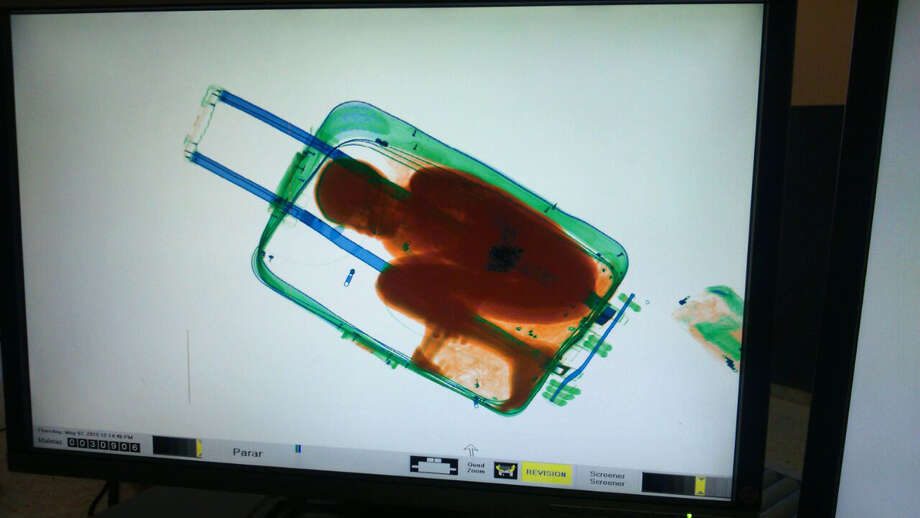 In this photo released by the Spanish Guardia Civil on Friday, May 8, 2015, a boy curled up inside a suitcase is seen on the display of a scanner at the border crossing in Ceuta, a Spanish city enclave in North Africa. A Spanish court has ordered the detention of a father who allegedly hid his 8-year-old son inside a closed suitcase in an attempt to smuggle the child illegally into Europe. A police statement said guards stopped a 19-year-old Moroccan woman who looked nervous as she waited in line Thursday at the land border crossing in Ceuta Photo: Spanish Interior Ministry,  Via AP, AP / Spanish Interior Ministry