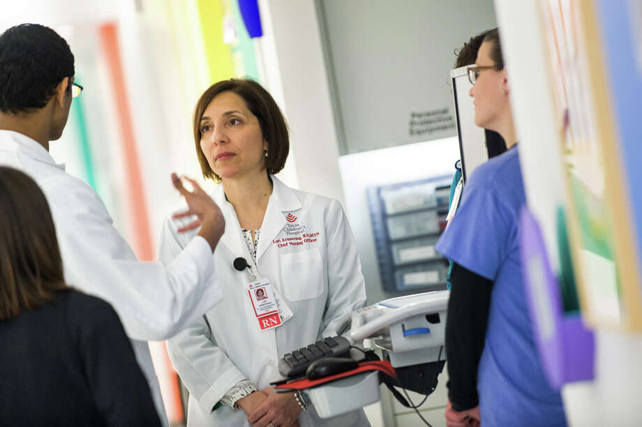 Lori Armstrong (center), chief nursing officer at Texas Children's Hospital, joins her staff at patient rounds. Armstrong leads her team through vision and example, and believes nurses play a critical role at every level. Photo: _