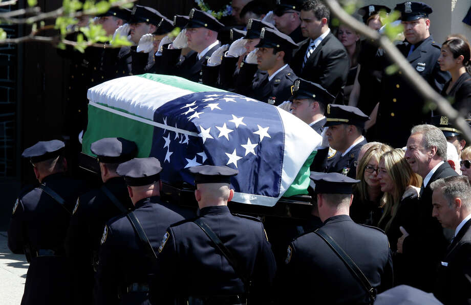 The family of New York City police officer Brian Moore watches as his casket is carried for his funeral. Photo: Mary Altaffer / Associated Press / AP