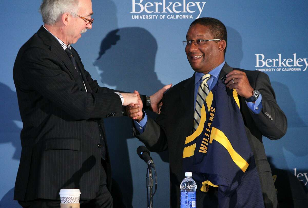 Nicholas Dirks, left, chancellor of University of California, Berkeley, presents Michael Williams with a jersey after naming him Cal's new athletic director during a news conference at the school's Haas Pavilion, Friday, May 8, 2015, in Berkeley, Calif.