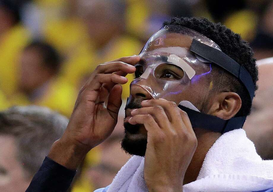 FILE - In this May 5, 2015, file photo, Memphis Grizzlies guard Mike Conley adjusts his mask during the first half of Game 2 in a second-round NBA playoff basketball series against the Golden State Warriors in Oakland, Calif. Conley's gritty comeback got the Memphis Grizzlies on track and stole home-court advantage away from the Golen State Warriors in their Western Conference series. (AP Photo/Ben Margot, File) Photo: Ben Margot / Associated Press / AP
