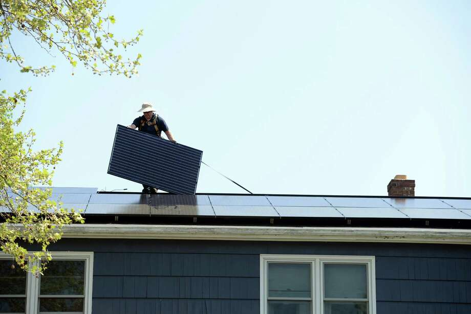 Todd Fowler, of Encon Solar, installs solar panels on the roof of a home on Apple Hill Drive in Milford Friday, May 8, 2015. Photo: Autumn Driscoll / Connecticut Post