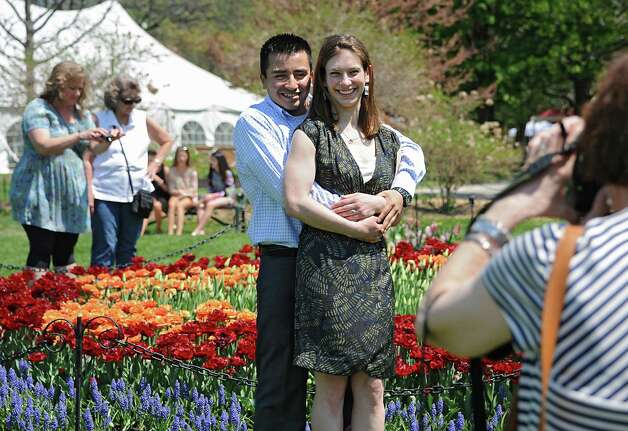 Jan Coles of Slingerlands, right, takes a photo of her daughter Emily Rochac Argueta and her husband Carlos Rochac Argueta in Washington Park during the start of the 167th annual Tulip Festival on Friday, May 8, 2015 in Albany, N.Y. The couple were married last May in a small civil ceremony. Tomorrow they will have a church ceremony with family and friends. They wanted to take photos in the park today before it got to crowed. (Lori Van Buren / Times Union) Photo: Lori Van Buren / 00031725A