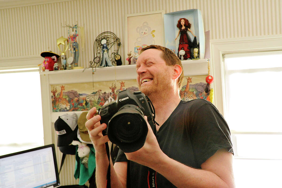 """Russ Murray cracks up as he takes a photograph in his home office in Stamford, Conn., on Wednesday, April 29, 2015. Russ says he does """"serious haiku and photography."""""""