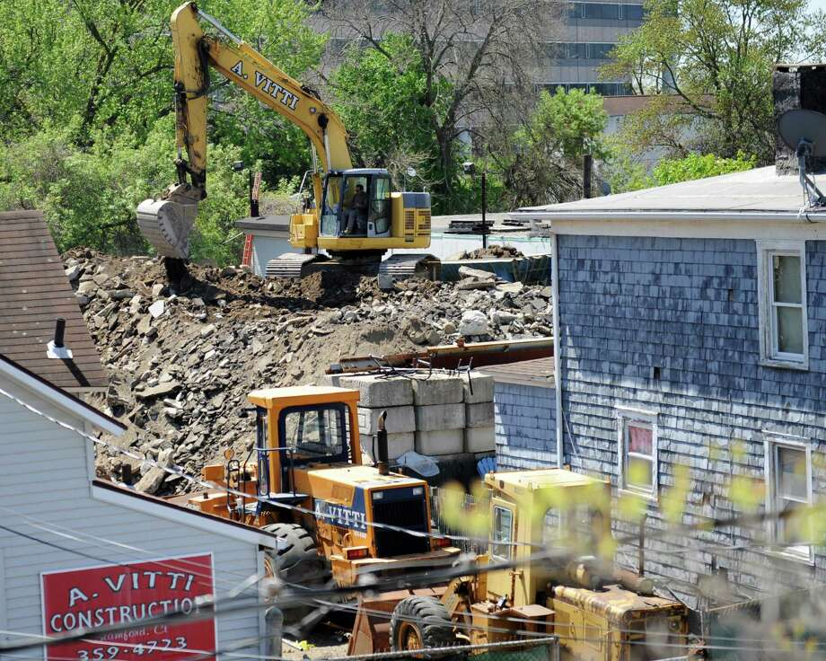 A construction vehicle crushes rocks in the A. Vitti Construction yard in Stamford, Conn. Thursday, May 7, 2015.  Neighbors say the noise and dust from the Vitti yard has been a nuisance for many years. Photo: Tyler Sizemore / Greenwich Time