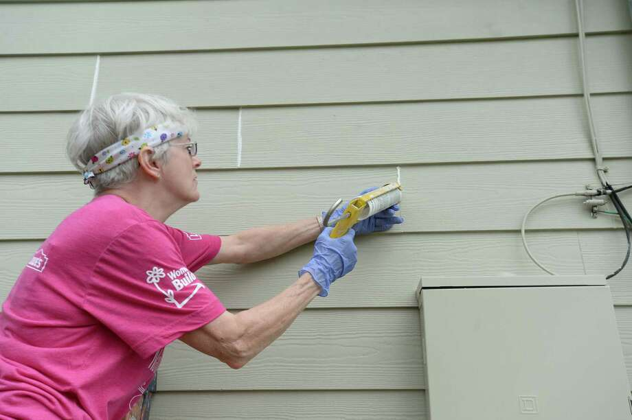 Marissa Paltz caulks exterior siding while she and co-workers from Strong, Pipkin, Bissell & Ledyard, LLP, work on rehabbing a home on Jenard in Beaumont's north end Wednesday. This week is Habitat for Humanity's National Women Build Week, where female volunteers from businesses throughout the country will turn out to build and rehabilitate home for Habitat families. This is the fifth year the firm has participated in the event. The property on Jenard is one of 34 homes Habitat for Humanity of Jefferson County built on land donated by the Archdiocese of Beaumont. The wooded land was cleared and converted into a neighborhood of entirely Habitat homes. The project gained speed after Hurricane Rita, with volunteers from across the nation turning out to assist in building the development. Photo taken Wednesday, May 6, 2015 Kim Brent/The Enterprise Photo: Kim Brent / Beaumont Enterprise