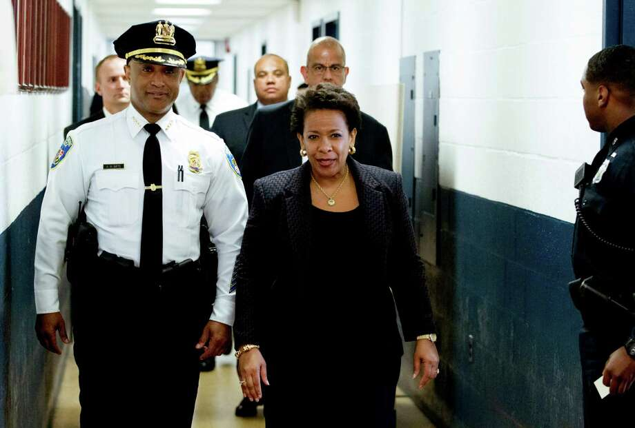Attorney General Loretta Lynch, accompanied by Baltimore Police Commissioner Anthony Batts, walks to meet with Baltimore police officers during a recent visit in Baltimore. A reader says that charges of homicide and abuse of power against six officers may help the city heal. Photo: JOSE LUIS MAGANA /New York Times / POOL