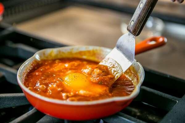 A peek at the pan as Chef Suzette Gresham prepares Italian Tomato Eggs. Burlingame, California at Riggs Distributing, Inc., Tuesday, March 17, 2015