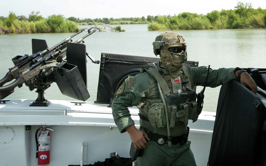 In this file photo, a masked Texas Department of Public Safety trooper prepares to patrol the Rio Grande River between McAllen, Texas, and Reynosa, Tamaulipas, Mexico, on a boat armed with M240 machine guns. The Legislature is now considering a massive boost to DPS to sustain the effort — $800 million more approved by the state Senate, $500 million more in the House. Given that the DPS contribution to drug interdiction amounts to less than 10 percent, this is throwing good money after bad results. Photo: Jay Janner /Associated Press / Austin American-Statesman