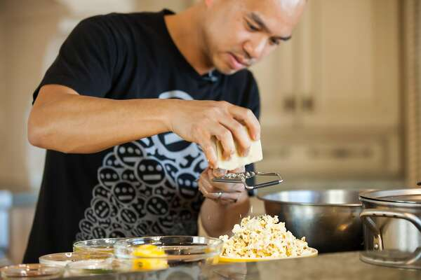 Chef James Syhabout adds a touch of parmesian cheese to the Ceasar Popcorn.