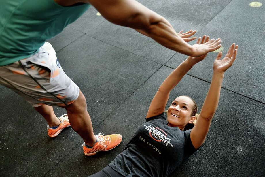Chef Lisa Astorga-Watel, owner of Bite restaurant, high-fives her friend and workout partner Paul Villaflor, left, during a CrossFit workout at Body Armor gym in San Antonio on Wednesday, April 22, 2015. Astorga-Watel has been doing CrossFit for over a year now. Photo: Matthew Busch /For San Antonio Express-News / © Matthew Busch