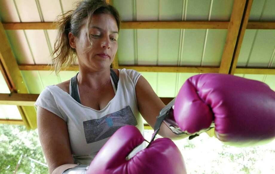 Tim McDiarmid, owner of Tim the Girl, dons gloves for a workout. Photo: Billy Calzada /San Antonio Express-News / San Antonio Express-News