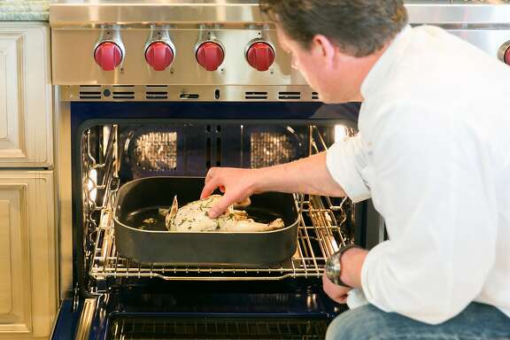 Tyler Florence  continues to check on the slow roasting chicken throughout the 2 hour cooking time. Burlingame, California at Riggs Distributing, Inc., Friday March 27, 2015.