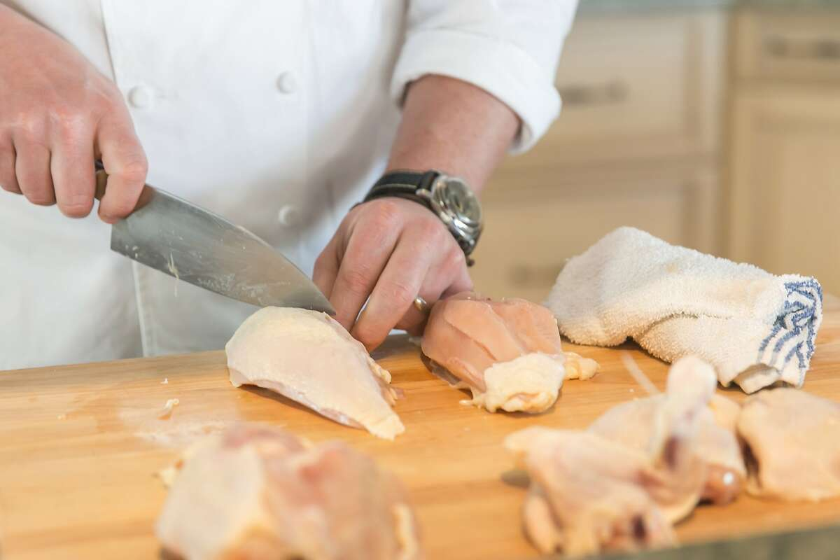 Tyler Florence demonstrates how to cut a whole chicken. Burlingame, California at Riggs Distributing, Inc., Friday March 27, 2015.
