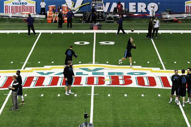 UCLA football players warm up on the field prior to the start of the Valero Alamo Bowl at the Alamodome on Jan. 2, 2015.