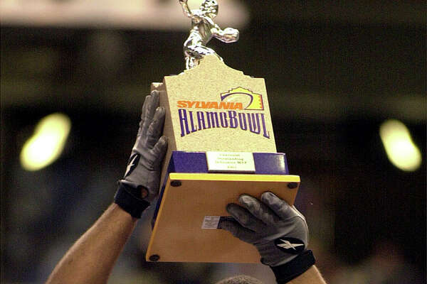 Iowa lineman Derrick Pickens holds up the defensive MVP award after the Hawkeyes beat Texas Tech 19-16 in the Alamo Bowl on Dec. 29, 2001 at the Alamodome.