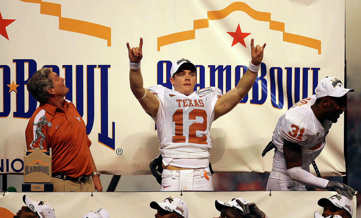 """Longhorns' Colt McCoy (center) gestures the """"Hook 'em Horns"""" sign before he receives the offensive player of the game as head coach Mac Brown (left) and defensive player of the game Aaron Ross (right) join McCoy on stage after defeating the Iowa Hawkeyes 26-24 to win the 2006 Alamo Bowl at the Alamodome on Dec. 30, 2006."""