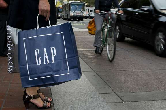 A pedestrian carriers a Gap Inc. shopping bag while waiting to cross Market Street in San Francisco, California, U.S., on Monday, July 7, 2014. U.S. same-store sales fell 1.2 percent month over month, according to the latest data released by Johnson Redbook Research. Photographer: David Paul Morris/Bloomberg