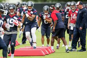 Third-round pick Jaelen Strong, center, learns ball protection during Friday's rookie minicamp workout. Strong says he is focused on listening to the coaches and getting into his playbook to learn the Texans' offense.