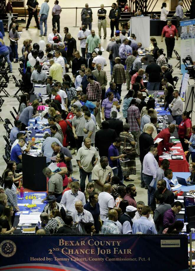 A crowd of applicants slowly make their way from table to table in search of job opportunities at the 2nd Chance Job Fair hosted by Bexar County Commissioner Tommy Calvert on Thursday at the AT&T Center. Photo: Kin Man Hui /San Antonio Express-News / ©2015 San Antonio Express-News