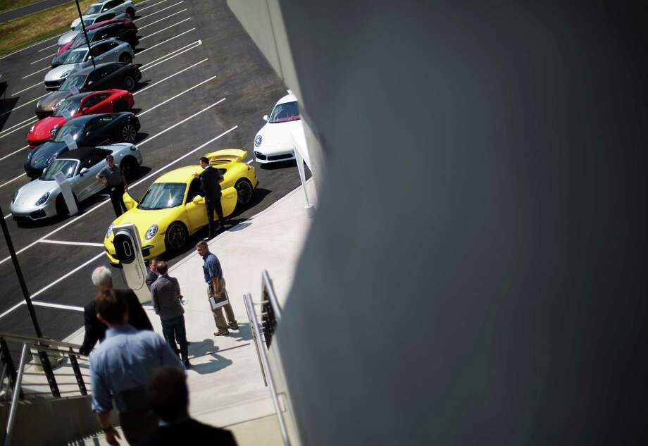 Guests walk down to waiting cars to take test drives on a track at the opening of Porsche's new North American headquarters, dubbed the Porsche Experience Center, Thursday, May 7, 2015, in Atlanta. The 27-acre complex is located on the former site of a Ford Motor Co. assembly plant that was in production for almost 60 years at the edge of Hartsfield-Jackson Atlanta International Airport. It is the sports-car company's largest investment outside of Germany. (AP Photo/David Goldman) Photo: David Goldman, STF / AP