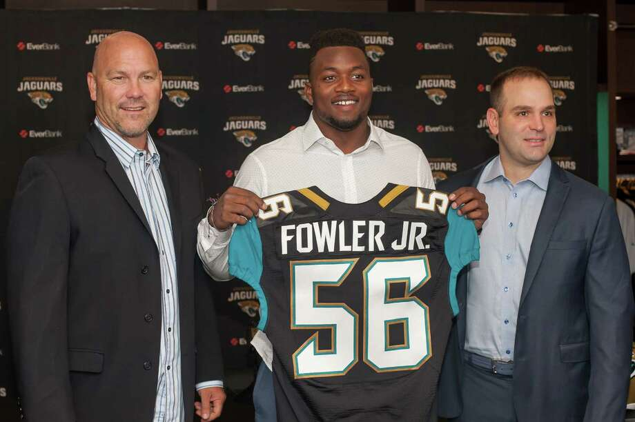 Dante Fowler, the Jacksonville Jaguars first round draft pick, holds up his jersey as he stands between head coach Gus Bradley, left, and general manager David Caldwell during an NFL football press conference at EverBank Field in Jacksonville, Fla., Saturday May 2, 2015. (Fran Ruchalski/The Florida Times-Union via AP) Photo: Fran Ruchalski, MBI / The Florida Times-Union