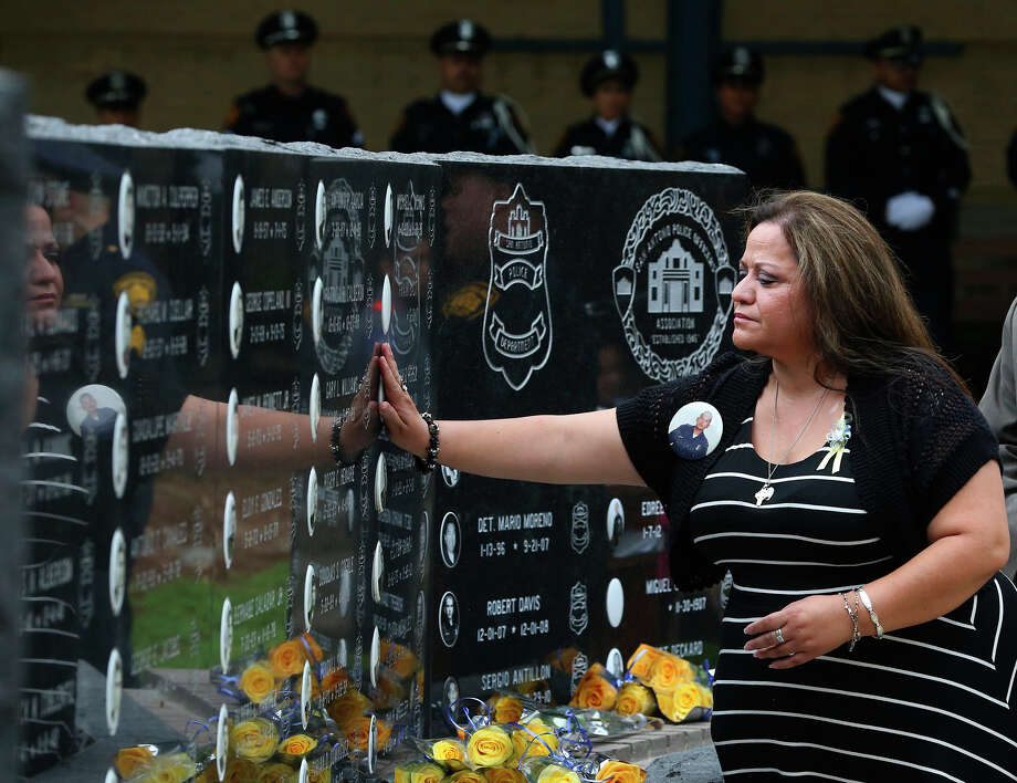 Liz Perez touches the police memorial wall as she pays homage to her brother, Oscar D. Perez, who died in the line of duty in 2000. Photo: Photos By John Davenport /San Antonio Express-News / ©San Antonio Express-News/John Davenport