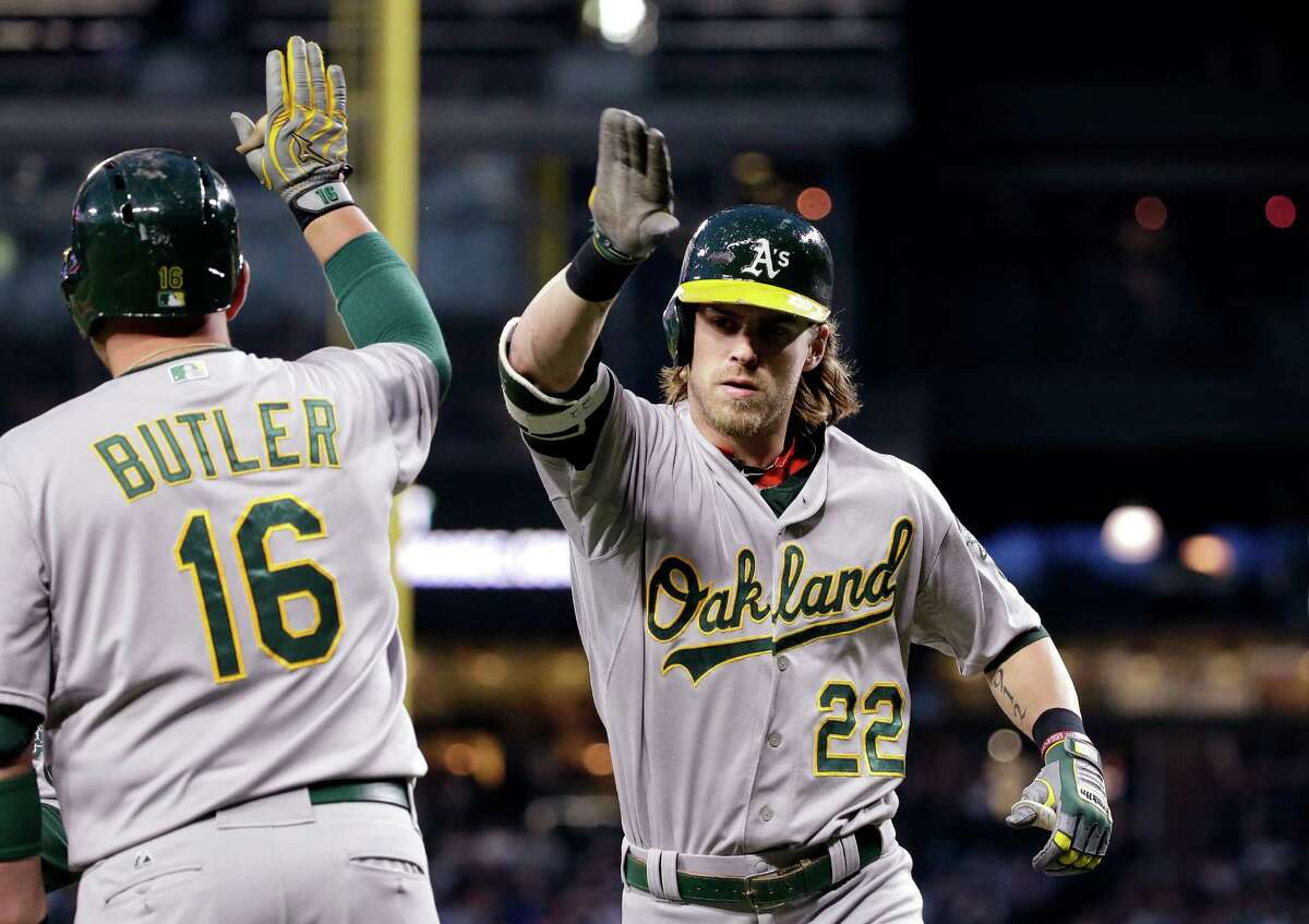 Oakland Athletics' Josh Reddick (22) is congratulated by on-deck batter Billy Butler on Reddick's two-run home run against the Seattle Mariners in the fifth inning of a baseball game Friday, May 8, 2015, in Seattle. (AP Photo/Elaine Thompson)