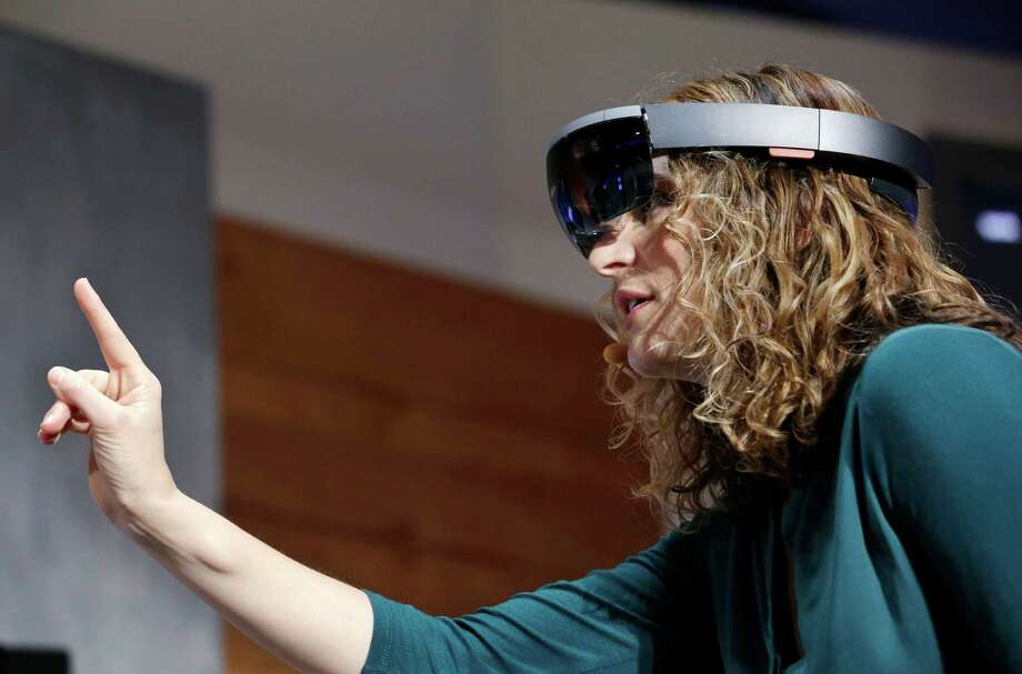 """Microsoft's Lorraine Bardeen demonstrates a HoloLens this year. It's a sci-fi-style """"augmented reality"""" headset that projects virtual objects in plain sight. Photo: Elaine Thompson, STF / AP"""