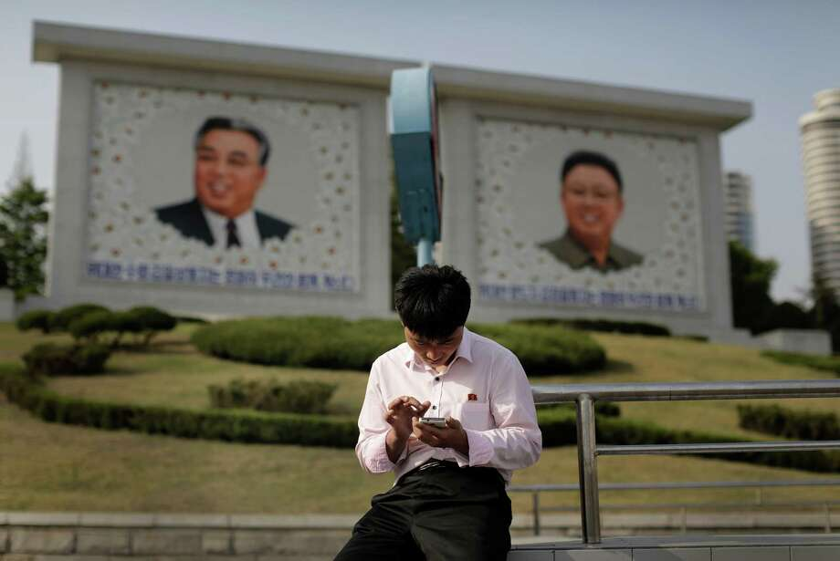 A man uses his smartphone as he sits in front of portraits of the late North Korean leaders Kim Il Sung, left, and Kim Jong Il. A North Korean online shopping site works not on the World Wide Web but on the nation's own intranet. Photo: Wong Maye-E, STF / AP