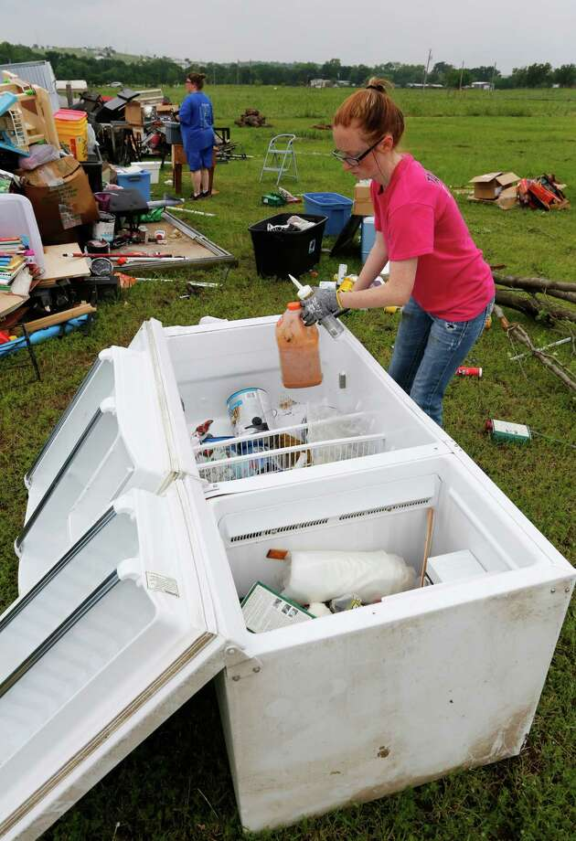 Sapphire Love uses a refrigerator as storage for recovered items as  neighbors and friends help clean up after Thursday night's tornado passed the area on Friday, May 8, 2015 in New Fairview, Texas.  Strong storms spawned several tornadoes and dumped heavy rain on North Texas overnight, flooding roads and damaging train tracks in an area where a freight train derailed before dawn on Friday, officials said.   (David Kent/The Fort Worth Star-Telegram via AP)  MAGS OUT; (FORT WORTH WEEKLY, 360 WEST); INTERNET OUT Photo: David Kent / Associated Press / The Fort Worth Star-Telegram