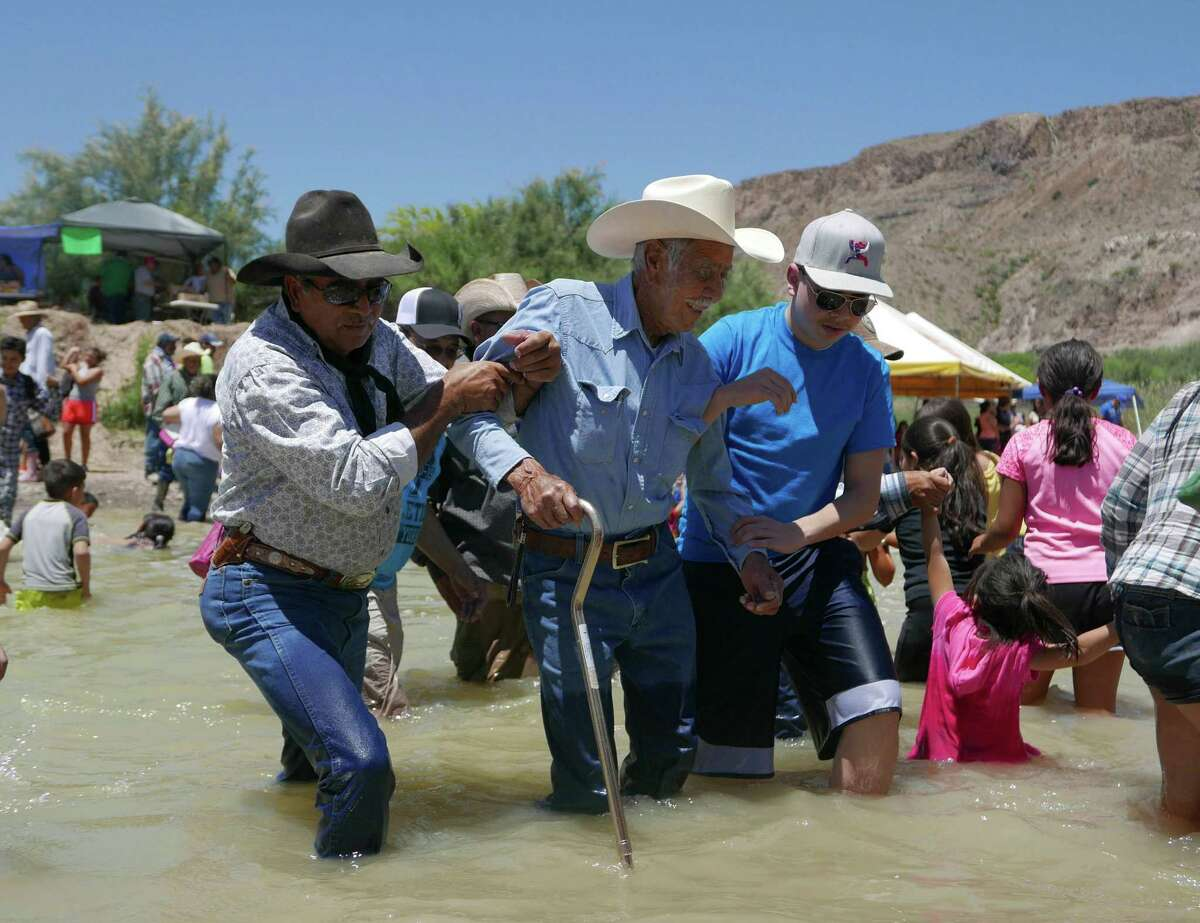 An elderly man is helped across the Rio Grande from Mexico to Texas during the Voices From Both Sides festival held at Lajitas, Texas, on Saturday, May 9, 2015. Many people from Mexico and the United States gathered and in some cases reunited with family members that they have not seen for years because of the border.