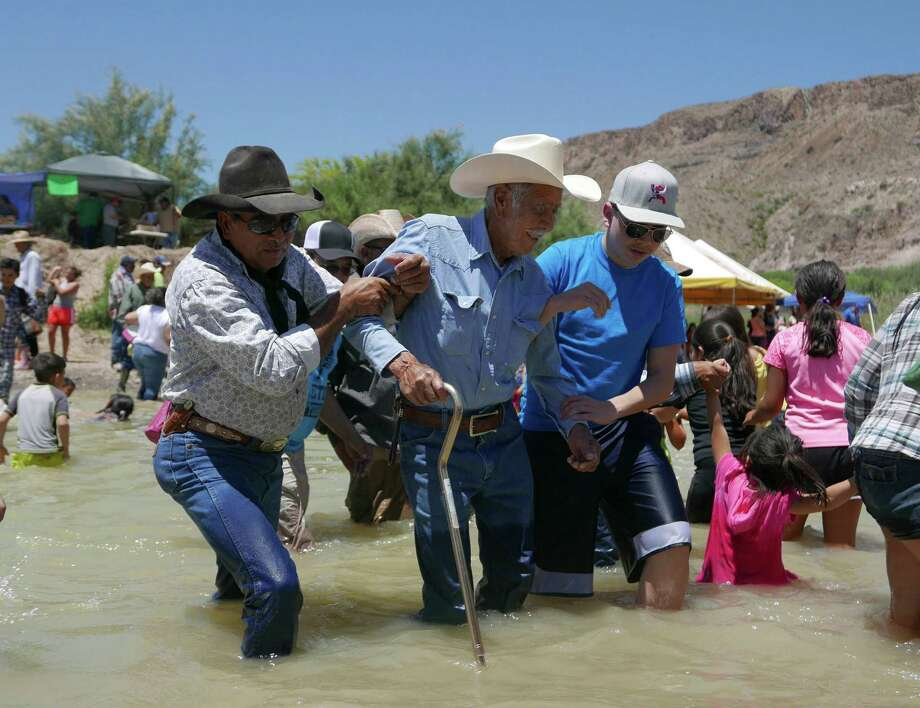 An elderly man is helped across the Rio Grande from Mexico to Texas during the Voices From Both Sides festival held at Lajitas, Texas, on Saturday, May 9, 2015. Many people from Mexico and the United States gathered and in some cases reunited with family members that they have not seen for years because of the border. Photo: Billy Calzada, Staff / San Antonio Express-News / San Antonio Express-News